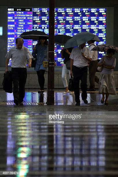 Pedestrians holding umbrellas cross a road in front of an electronic board outside a securities firm in Tokyoin Tokyo Japan on Wednesday Sept 10 2014...