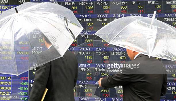 Pedestrians holding umbrellas look at an electronic stock board outside a securities firm in Tokyo Japan on Monday Feb 18 2013 The yen fell against...