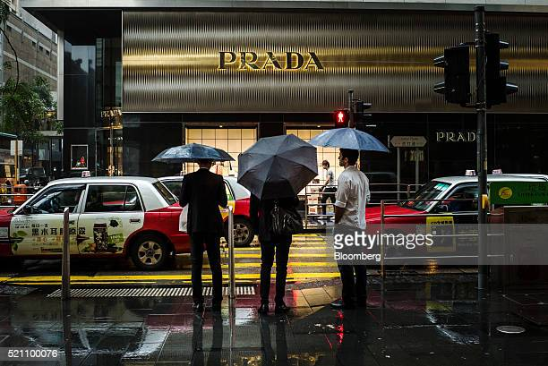Pedestrians holding umbrellas wait to cross a road in front of a Prada SpA luxury fashion store in the Central district of Hong Kong China on...