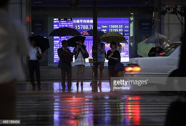 Pedestrians holding umbrellas wait to cross a road in front of an electronic board displaying the closing figure of the Nikkei 225 Stock Average...
