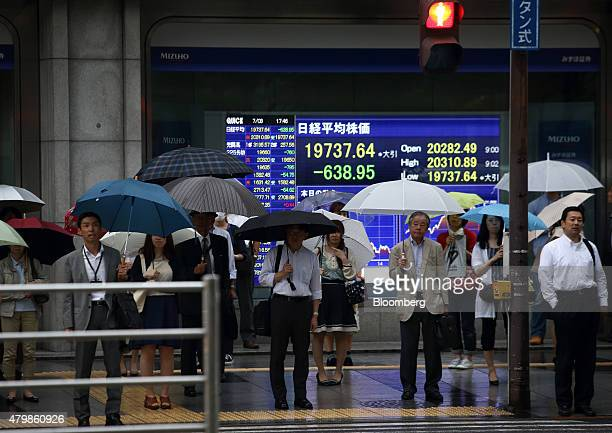 Pedestrians holding umbrellas wait to cross a road in front of an electronic stock board displaying the closing figure of the Nikkei 225 Stock...