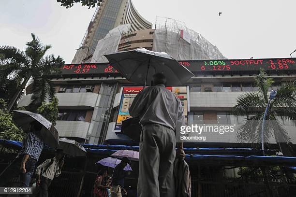 Pedestrians holding umbrellas walk past an electronic ticker board displaying stock figures at the Bombay Stock Exchange which stands partially...