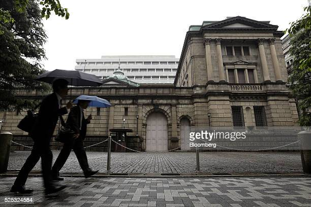 Pedestrians holding umbrellas walk past the Bank of Japan headquarters in Tokyo Japan on Thursday April 28 2016 The BOJ held off on expanding...