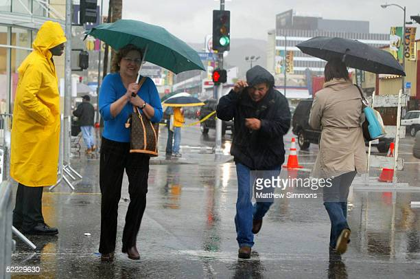 Pedestrians hurry in the rain to cross Hollywood Boulevard during preparations for the 77th Academy Awards outside the Kodak Theatre on February 22,...