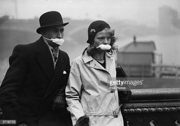 Pedestrians in a London street wearing masks over their mouths in an effort to avoid catching flu on the advice of a London doctor who suggested that...