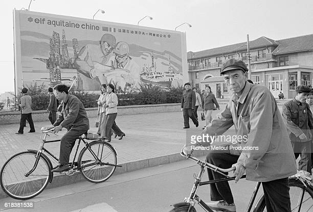 Pedestrians in Beijing's Tiananmen Square pass by a billboard for the French oil company Elf Aquitaine.
