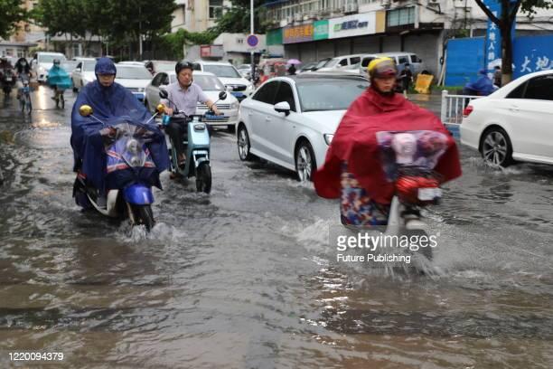Pedestrians in raincoats ride on a flooded road after a rainstorm in Nanjing City, Jiangsu Province, China, June 15, 2020.- PHOTOGRAPH BY Costfoto /...