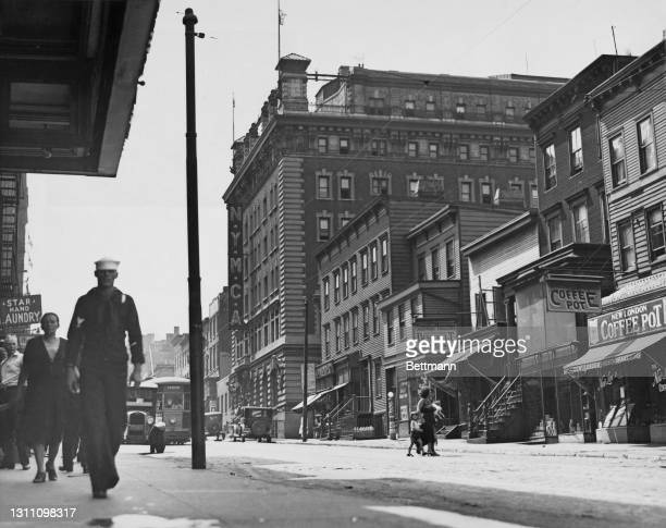 Pedestrians including a man in naval uniform in this view of the Sands Street Navy YMCA, among other businesses - including the Star Hand Laundy, and...