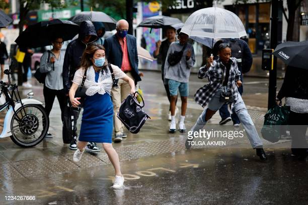 Pedestrians jump a puddle as they cross the road during heavy rain in central London on July 28, 2021.