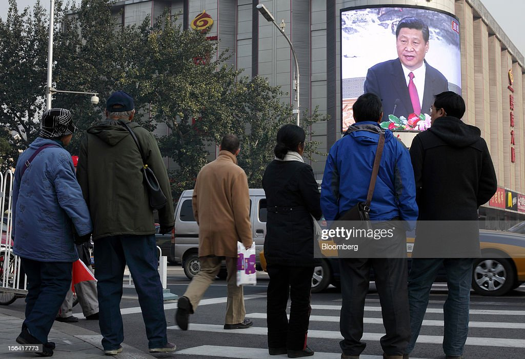 Pedestrians look at a monitor broadcasting a news conference by Xi Jinping, general secretary of the Communist Party of China, outside a subway station in Beijing, China, on Thursday, Nov. 15, 2012. Xi replaced Hu Jintao as head of the Chinese Communist Party and the nation's military, ushering in the fifth generation of leaders who are set to run the world's second-biggest economy over the next decade. Photographer: Tomohiro Ohsumi/Bloomberg via Getty Images