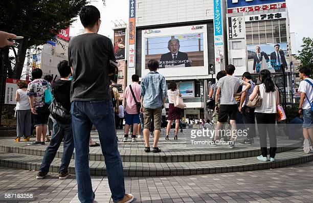Pedestrians look at a monitor showing Japan's Emperor Akihito delivering a speech in a video message on August 8 2016 in Tokyo Japan Japan's Emperor...