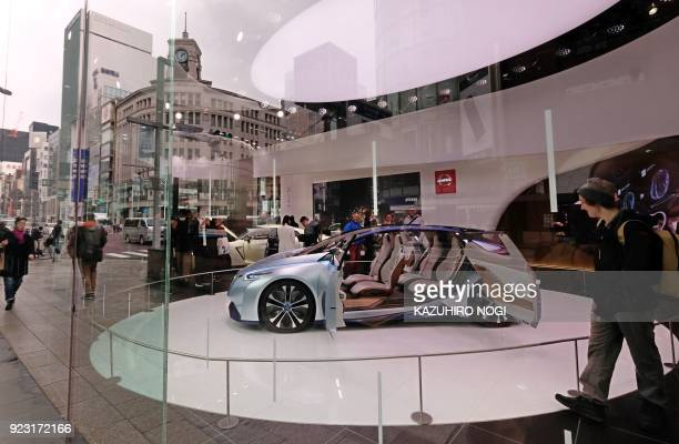Pedestrians look at a new car exhibited at a showroom in Tokyo on February 23 2018 Japan's consumer prices edged up 09 percent in January government...