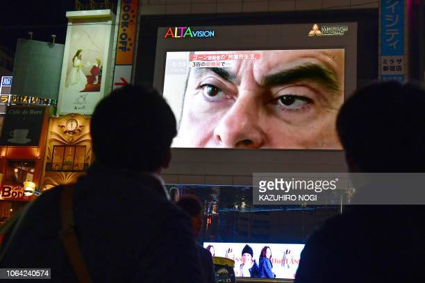 TOPSHOT Pedestrians look at a screen showing a news programme featuring Nissan chairman Carlos Ghosn in Tokyo on November 22 2018 Top executives from...