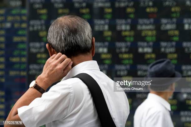 Pedestrians look at an electronic stock board outside a security firm on August 26, 2019 in Tokyo, Japan. Japanese stocks dropped and the yen climbed...