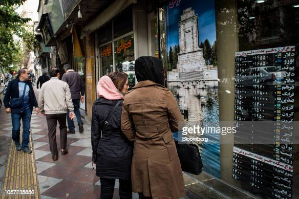 Pedestrians look at currency exchange rate information in the window of a store in Tehran Iran on Saturday Nov 3 2018 Irans Supreme Leader Ayatollah...
