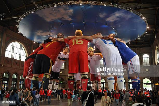 Pedestrians look at giant statues of players from different national football teams, Michael Ballack and Philipp Lahm from Germany, Karim Benzema and...