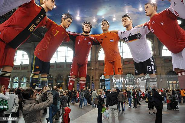 Pedestrians look at giant statues of players from different national football teams Michael Ballack and Philipp Lahm from Germany Karim Benzema and...