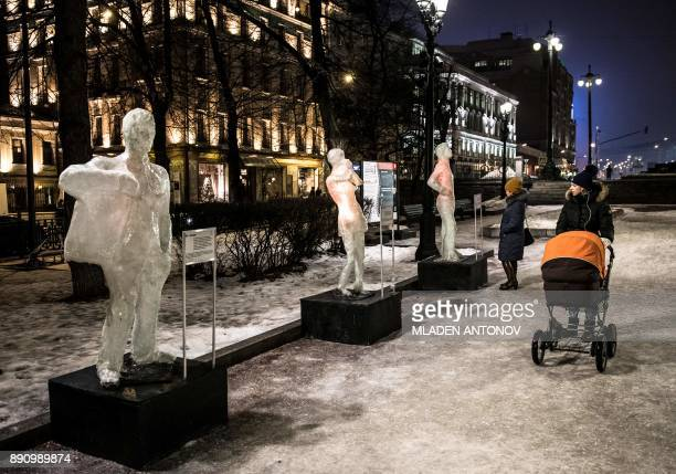 Pedestrians look at ice sculptures exhibited on the Boulevard ring to rise awareness of Bekhterev's disease in Moscow on December 12 2017 Ankylosing...