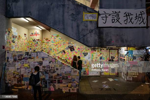 Pedestrians look at notes on a makeshift Lennon Wall at a flight of stairs in Sai Wan Ho district on July 20 2019 in Hong Kong China Lennon Wall...