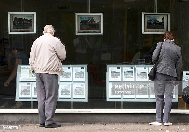 Pedestrians look at properties advertised for sale in an estate agent's window in Hornchurch UK on Tuesday Aug 11 2009 The UK housing market improved...