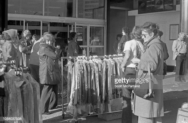 Pedestrians look at racks of clothing during an unspecified department store's sidewalk sale on Queens Boulevard in Queens New York New York...