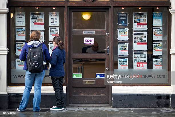 Pedestrians look at residential properties displayed for sale in the window of an estate agents in London UK on Tuesday Nov 12 2013 Under Bank of...