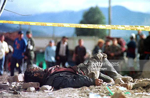 Pedestrians look at the body of a mortar bomb victim August 7 2002 in Bogota Colombia Approximately ten people died and 46 others were injured when...