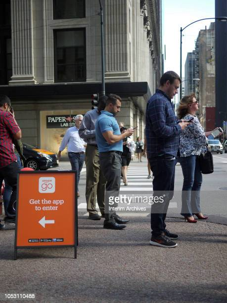 Pedestrians look at their phones while waiting for the light to change on the northwest corner of South Clark and West Adams streets in Chicago...
