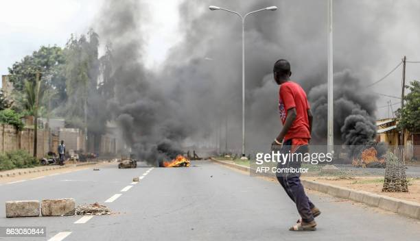 Pedestrians look on as a barricade burns at a crossroads in Be Lome on October 19 2017 Protesters erected makeshift barricades and blocked roads in...