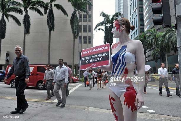 Pedestrians look on as a member of animal rights group People for the Ethical Treament of Animals wearing body paint in order to resemble a bloodied...