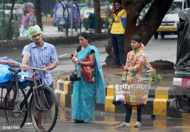 Pedestrians look on the daily market area in Bhubaneswar India on 16 November 2017 and wear rain court and holds umbrella to protect from low...