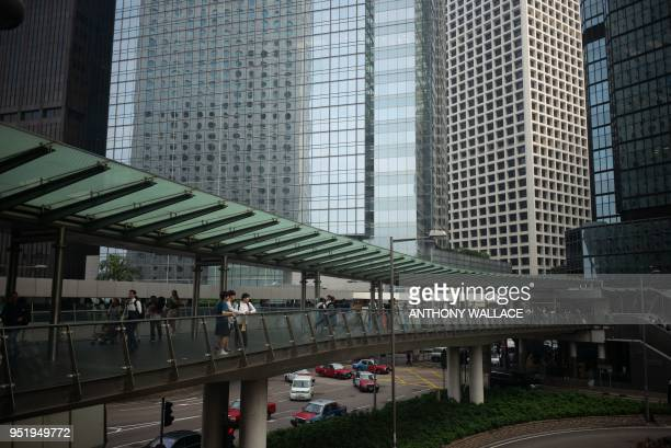 Pedestrians look out from a footbridge in the Central district of Hong Kong on April 27 2018