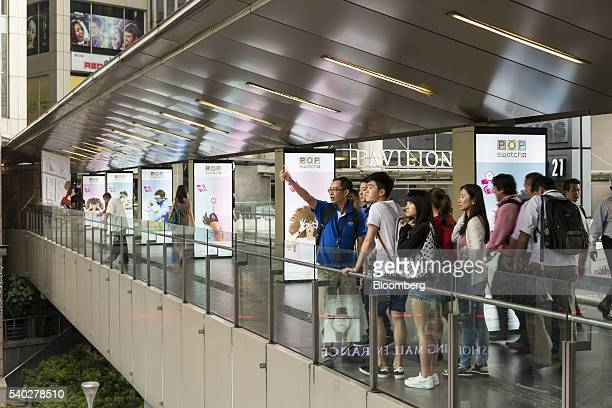 Pedestrians look out from a skywalk leading to the Pavilion shopping mall in Kuala Lumpur Malaysia on Tuesday June 14 2016 Consumer Price Index...