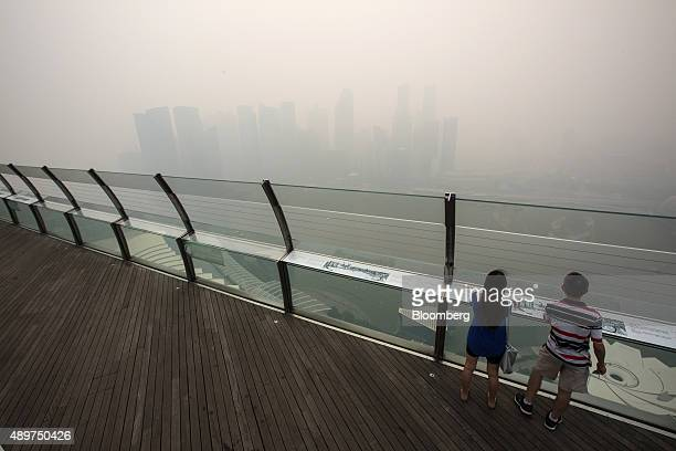 Pedestrians look out towards the city skyline at Marina Bay as buildings in the central business district stand shrouded in smog in Singapore, on...