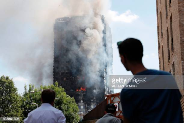 TOPSHOT Pedestrians look up towards Grenfell Tower a residential block of flats in west London on June 14 as firefighters continue to control a fire...