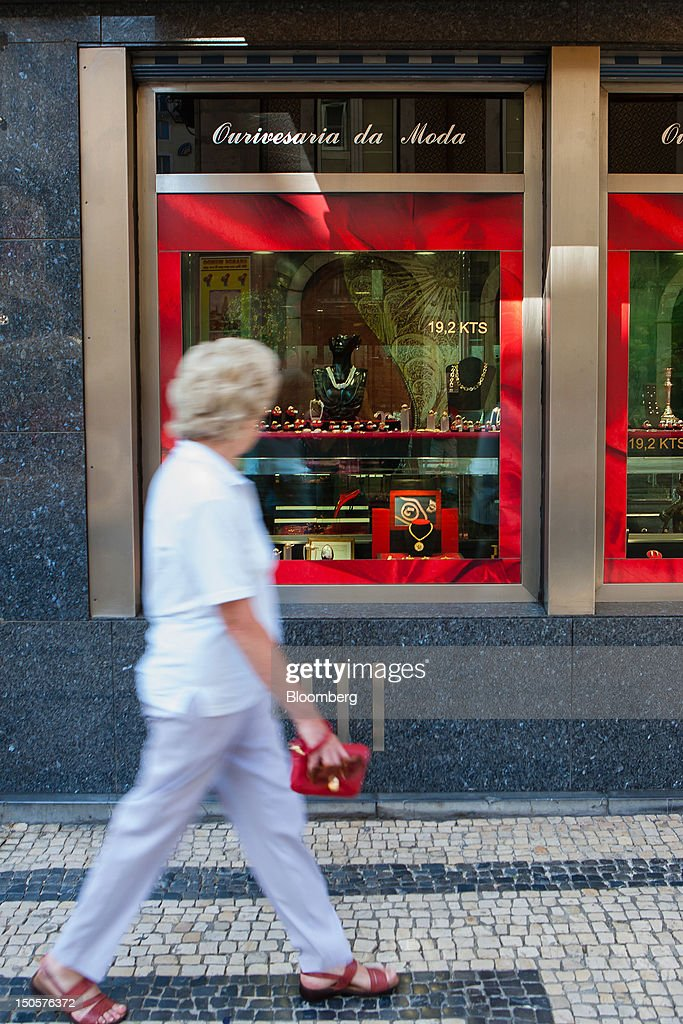 A pedestrians looks a gold jewelry on display in the window of a jewelry store in Lisbon, Portugal, on Wednesday, Aug. 22, 2012. In Portugal, the historical home of some of Europe's biggest gold reserves, the number of jewelry stores, which include cash-for-gold shops, increased 29 percent in 2011 from a year earlier, a study commissioned by parliament found. Photographer: Mario Proenca/Bloomberg via Getty Images