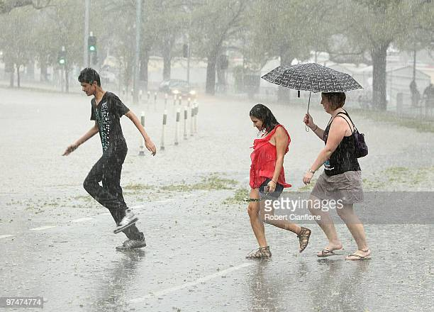 Pedestrians looks to get out of heavy rain as Batman Avenue is flooded as massive storms hit Melbourne city on March 6, 2010 in Melbourne, Australia....