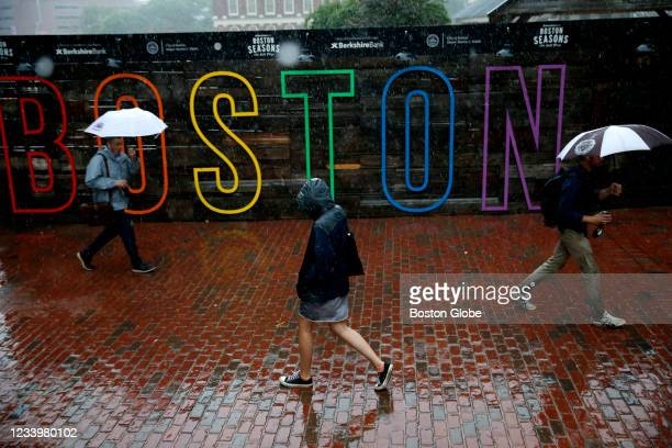 Pedestrians make their way across City Hall Plaza in Boston in the rain on July 12, 2021.