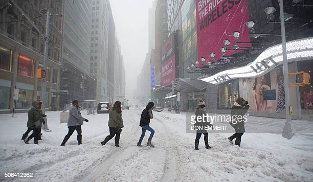 Pedestrians make their way across snow covered Broadway January 23 2016 in New York A deadly blizzard with bonechilling winds and potentially...