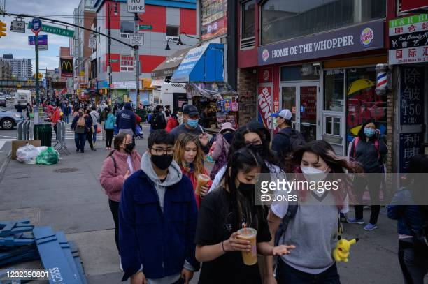 Pedestrians make their way along a street in Flushing, in the New York borough of Queens on April 18, 2021. - Anti-Asian hate crimes almost tripled...