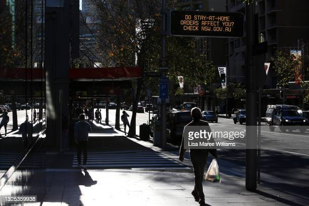 Pedestrians make their way along Oxford Street ahead of lockdown restrictions being imposed on June 25, 2021 in Sydney, Australia. Residents who live...