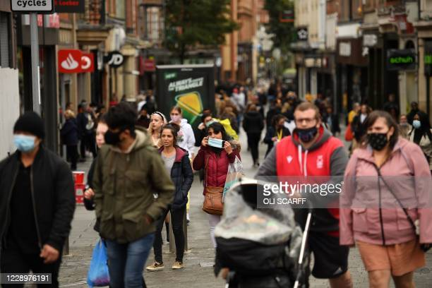 Pedestrians, many wearing protective face coverings to combat the spread of coronavirus covid-19 walk through central Nottingham in central England...