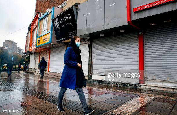 Pedestrians, mask-clad due to the COVID-19 coronavirus pandemic, walk past closed shops along a street in Iran's capital Tehran on November 21 as the...