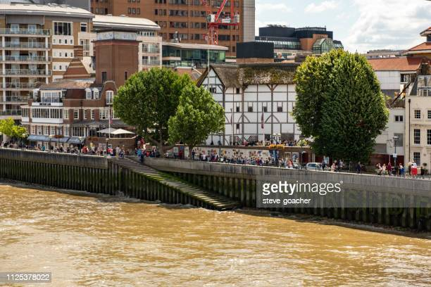 pedestrians milling around the shakespeare's globe theatre on the south bank of london's river thames. - elizabethan era stock photos and pictures