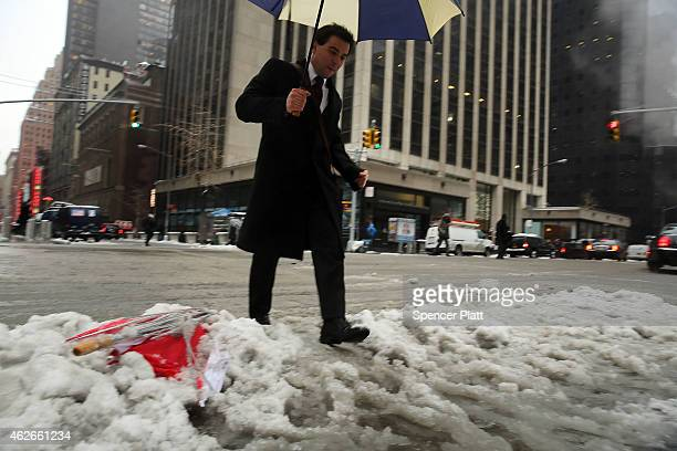 Pedestrians navigate the snow ice and puddles along Manhattan's streets on February 2 2015 in New York City Another winter storm has brought...