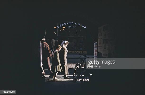 Pedestrians on a shopping street seen through an archway Belfast Northern Ireland June 1955 Original publication Picture Post 7825 Belfast pub 25th...