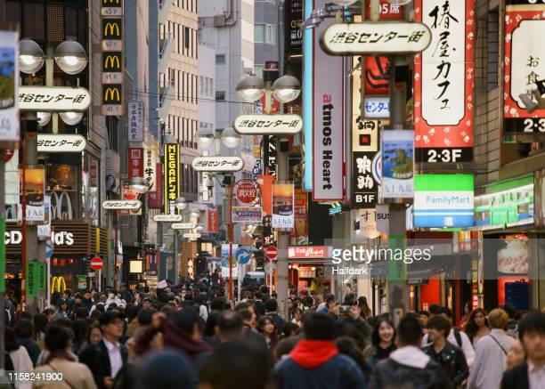 pedestrians on bustling modern city street, shibuya, tokyo, japan - escritura japonesa fotografías e imágenes de stock