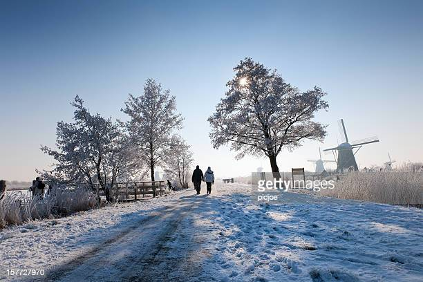 pedestrians on dyke near windmills at Kinderdijk in wintry landscape
