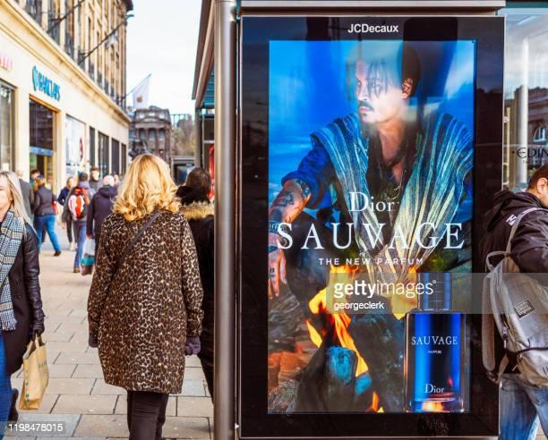 ディオール広告を通過するエディンバラ通りの歩行者 - プリンシズ通り ストックフォトと画像