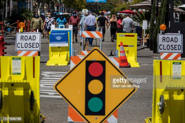 Pedestrians on Main Street where masks are required in public in the city of Ventura, which has opened up with restrictions on traffic and other...